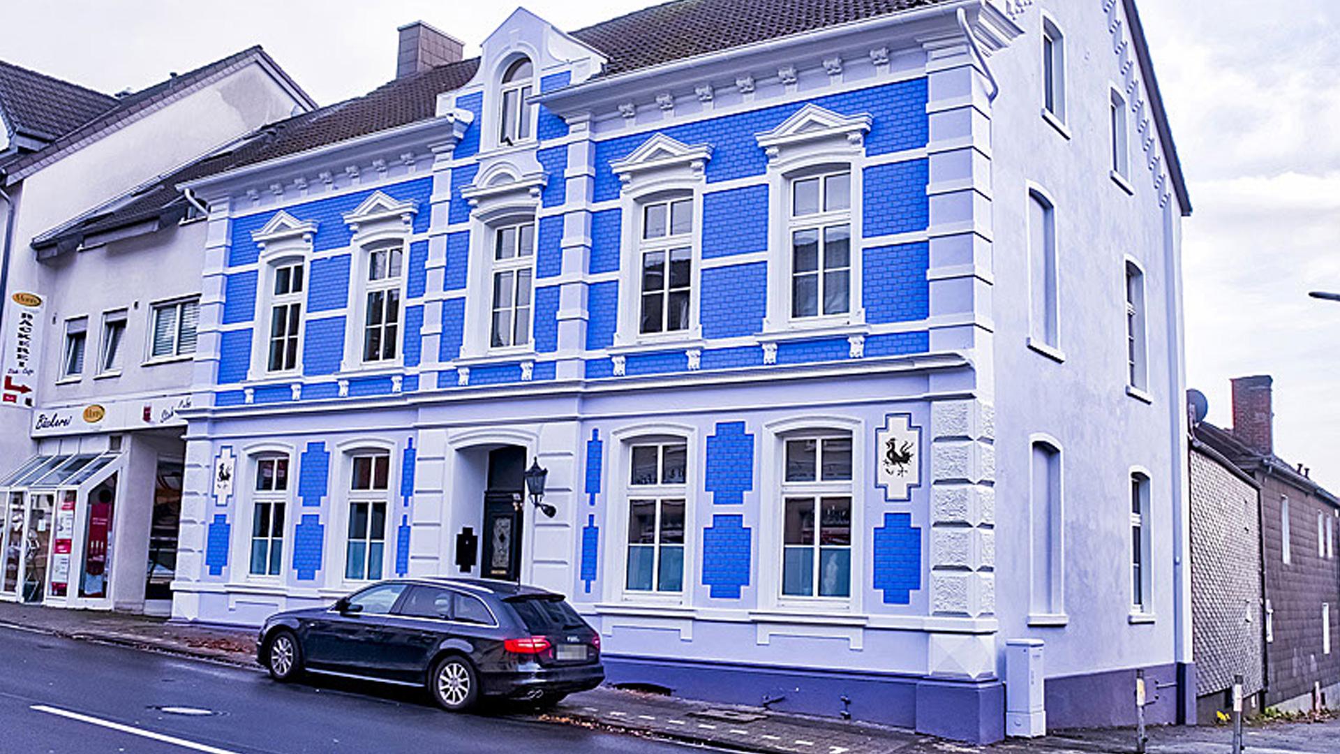 Die Außenfassade eines Altbaus mit blauen Ziegeln